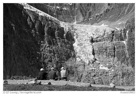 Hikers looking at a hanging glacier on  Mt Edith Cavell. Jasper National Park, Canadian Rockies, Alberta, Canada (black and white)