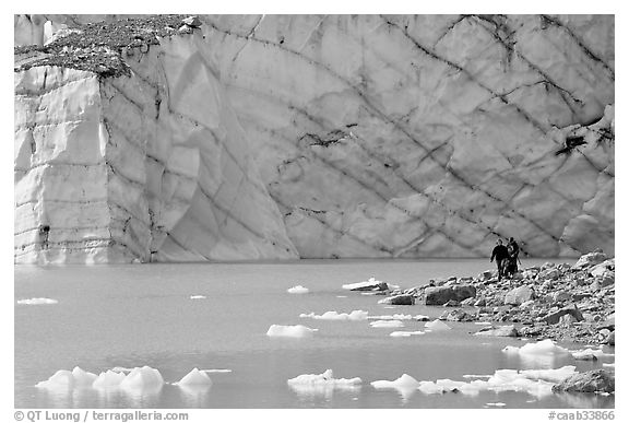 Hikers on the shore of Cavell Pond with high glacier wall behind. Jasper National Park, Canadian Rockies, Alberta, Canada (black and white)