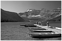 Dock and small boats, with tourists walking down, Cameron Lake. Waterton Lakes National Park, Alberta, Canada (black and white)