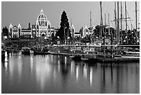Boats in inner harbor with a trail of lights and parliament building lights. Victoria, British Columbia, Canada ( black and white)