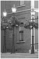 Street lamps with flower baskets and brick wall. Victoria, British Columbia, Canada (black and white)