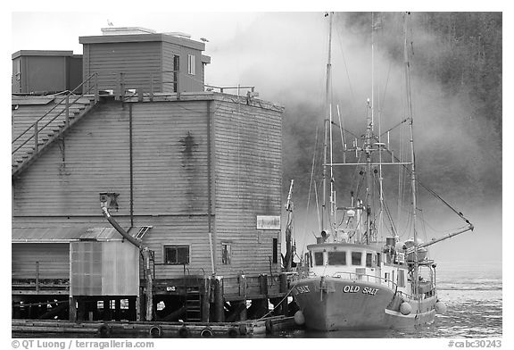 Commercial fishing boat next to a fishery, Tofino. Vancouver Island, British Columbia, Canada (black and white)