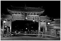 Gate of Harmonious Interest marking the entrance of Chinatown, night. Victoria, British Columbia, Canada ( black and white)