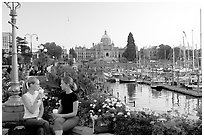 Women drinking coffee at the Inner Harbour, sunset. Victoria, British Columbia, Canada (black and white)