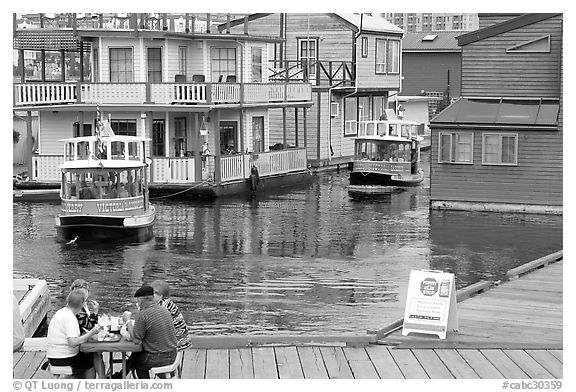 Harbor ferries and outdoor eatery, Upper Harbor. Victoria, British Columbia, Canada (black and white)