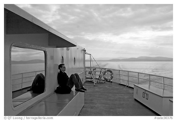 Passenger sitting on the deck of ferry. Vancouver Island, British Columbia, Canada (black and white)