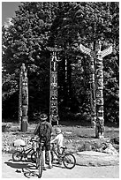 Family with bicycles looking at Totems, Stanley Park. Vancouver, British Columbia, Canada (black and white)