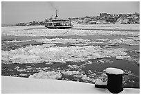 Ferry crossing the Saint Laurent river partly covered with ice, Quebec City. Quebec, Canada (black and white)