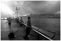 Fishing on the waterfront promenade, sunrise. Hong-Kong, China ( black and white)