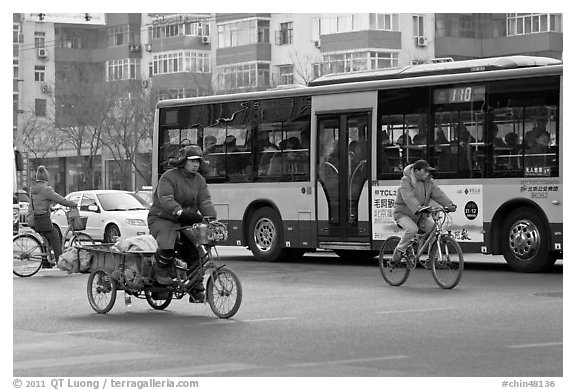 Tricyle, bicycles and bus on street. Beijing, China (black and white)