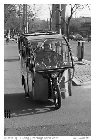Enclosed three wheel motorcycle on street. Beijing, China (black and white)