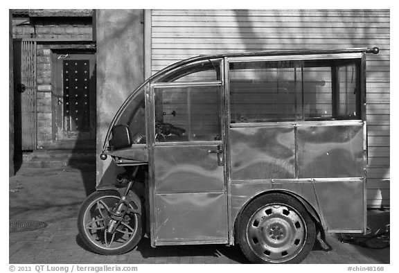 Enclosed scooter on sidewalk. Beijing, China (black and white)