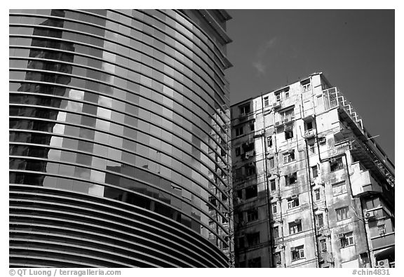Glass building aside an old building, Kowloon. Hong-Kong, China (black and white)