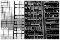 Glass building next to older buildings with air conditioners, Hong-Kong Island. Hong-Kong, China (black and white)
