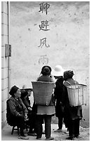 Elderly women with back baskets in front of a wall with Chinese scripture. Shaping, Yunnan, China (black and white)