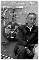 Man selling musical instruments. Shaping, Yunnan, China (black and white)