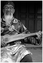 Elderly musician playing the a traditional guitar. Baisha, Yunnan, China ( black and white)