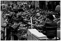 Woman checking out her bicycle at a bicycle lot. Kunming, Yunnan, China ( black and white)