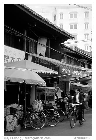 Man on bicycle in front of wooden buildings. Kunming, Yunnan, China (black and white)