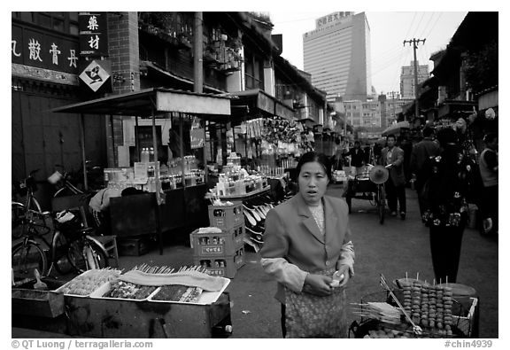 Street market in an old alley of wooden buildings, with a high rise in the background. Kunming, Yunnan, China (black and white)