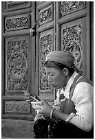 Bai woman eating from a bowl in front of carved wooden doors. Dali, Yunnan, China ( black and white)