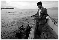 Cormorant fisherman feeds small fish to his birds as a prize for catching large fish. Dali, Yunnan, China ( black and white)