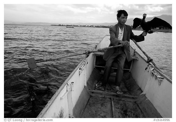 Fisherman holding a cormorant. Dali, Yunnan, China (black and white)
