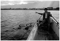 Cormorant Fisherman gives orders to his  fishing birds. Dali, Yunnan, China ( black and white)