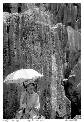 Woman from the Sani branch of the Yi tribespeople with a sun unbrella at the Stone Forest. Shilin, Yunnan, China (black and white)