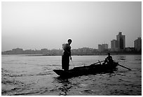 Fishermen at the confluence of the Dadu He and Min He rivers at sunset. Leshan, Sichuan, China ( black and white)