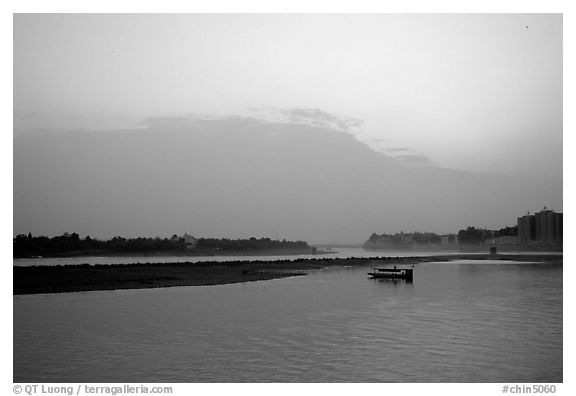 Boat at the confluence of the Dadu He and Min He rivers at sunset. Leshan, Sichuan, China (black and white)