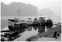 Boats along the river with misty cliffs in the background. Leshan, Sichuan, China (black and white)