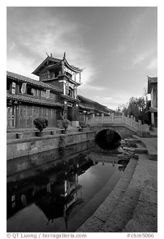 Kegong tower (memorial archway of imperial exam) reflected in canal, sunrise. Lijiang, Yunnan, China (black and white)