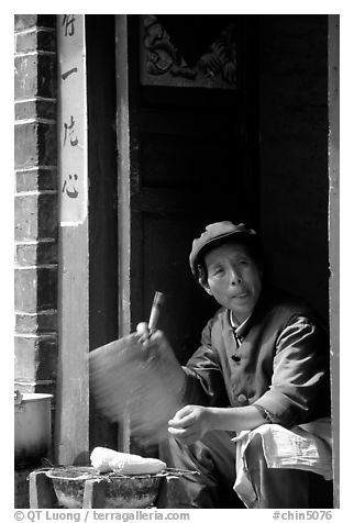 Naxi woman at doorway selling broiled corn. Lijiang, Yunnan, China (black and white)