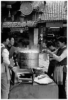 Naxi women selling dumplings and Naxi baba flatbread. Lijiang, Yunnan, China (black and white)