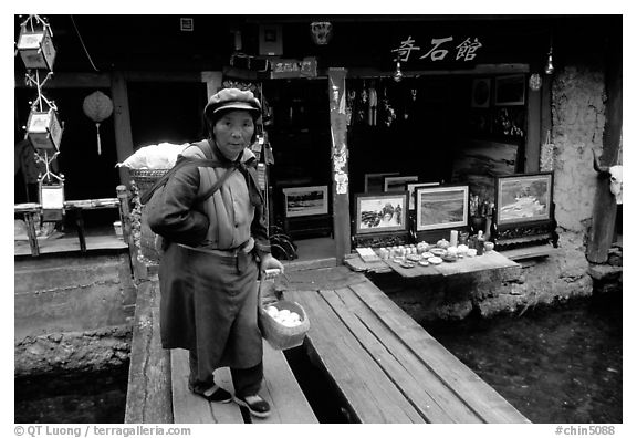 Naxi woman peddling eggs  to local residents walks acros a canal. Lijiang, Yunnan, China (black and white)