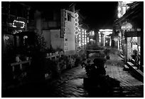 Red lanterns reflected in a canal at night. Lijiang, Yunnan, China (black and white)