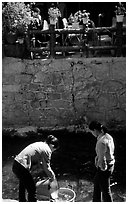 Women washing clothes in a canal. Lijiang, Yunnan, China (black and white)