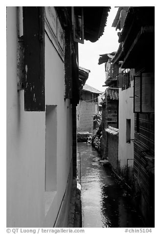 Canal sneaking narrowly between walls. Lijiang, Yunnan, China (black and white)