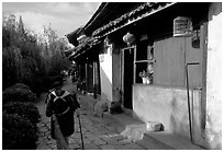 Naxi woman sweeps the floor at the door of her wooden house. Lijiang, Yunnan, China (black and white)