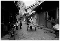 Early morning activity in a cobblestone street. Lijiang, Yunnan, China (black and white)