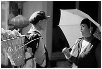 Two women conversing in the street. Lijiang, Yunnan, China (black and white)