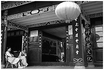 Women sit ouside  the Wufeng Lou (Five Phoenix Hall). Lijiang, Yunnan, China (black and white)
