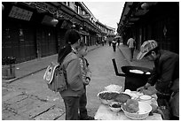 Schoolchildren get Naxi flatbread for breakfast. Lijiang, Yunnan, China (black and white)