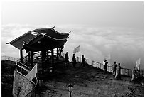 Monks and pilgrims admiring a sea of cloud from the summit. Emei Shan, Sichuan, China ( black and white)