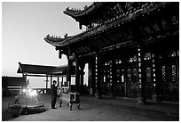 Pilgrim prays in the Jinding Si (Golden Summit) temple at dusk. Emei Shan, Sichuan, China ( black and white)