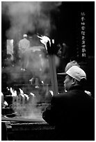Pilgrim offering big incense stick. Emei Shan, Sichuan, China (black and white)
