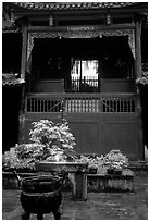 Buddha image seen from rainy courtyard of Hongchunping temple. Emei Shan, Sichuan, China (black and white)