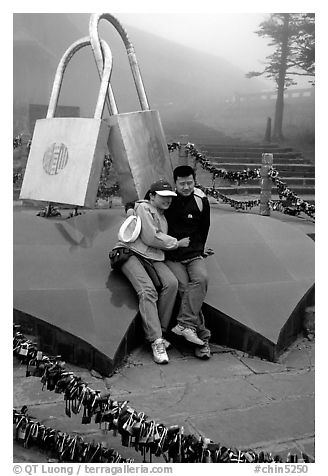 Lovers sit on top of two hearts surrounded by chain locks. Emei Shan, Sichuan, China (black and white)