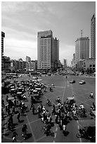 Pedestrians and bicyclists cross a major avenue. Chengdu, Sichuan, China ( black and white)